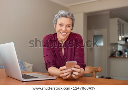 Smiling casual senior woman using laptop while messaging with smartphone. Happy mature woman working with a cellphone and laptop at home and looking at camera. Business woman using her mobile phone.