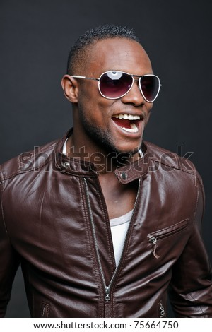 Smiling casual young black man wearing brown leather jacket and sunglasses. Studio portrait against dark background.