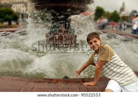 smiling caucasian boy by fountain - stock photo