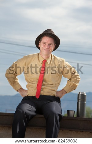 Smiling Caucasian businessman relaxes with hands on hips
