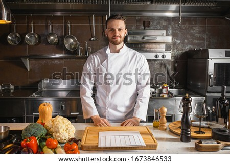 smiling caucasian cook man ready to cook in kitchen, wearing white apron. professional cook make perfect garnish and other delicious dishes. man look at camera. kitchen, restaurant, cook, food concept