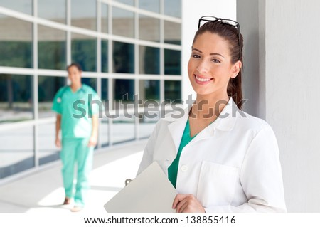 Smiling Caucasian doctor holding a clipboard in brightly lit exterior hospital environment in scrubs, white lab coat. Nurse in scrubs in the background.
