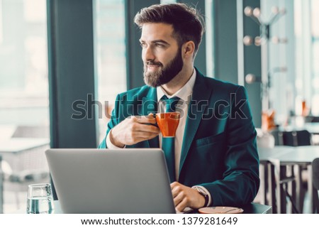 Smiling Caucasian elegant businessman drinking coffee in cafe, using laptop and looking trough window. Push yourself, because no one is going to do it for you.