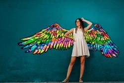 Smiling Caucasian girl in white summer dress posing in front of turquoise wall with colorful wings.