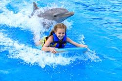 smiling Caucasian girl on wake board with dolphin in swimming pool