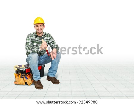 smiling caucasian handyman sit on toolbox