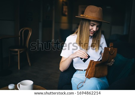 Smiling caucasian hipster girl dressed in trendy apparel and hat open her clutch for taking credit card spending time in cafe interior,cheerful young 20s woman in stylish cool clothes checking her bag stock photo