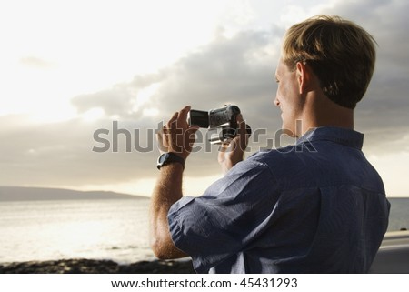 Smiling Caucasian man photographing a scenic sunset at a beach. Horizontal format.