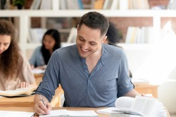Smiling Caucasian man sit at desk in library handwrite in notebook do homework or research, happy motivated male student prepare for exam or test in shared space, write make notes from books
