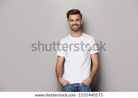 Photo of Smiling Caucasian man wearing casual clothes stand isolated on grey studio background look at camera posing, happy male model actor in white t-shirt hold hands in pockets shooting casting