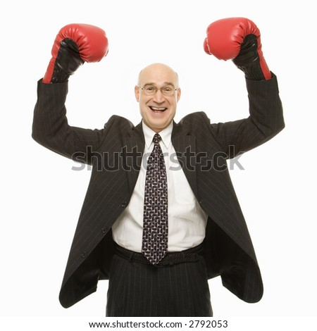 Smiling Caucasian middle-aged businessman standing with arms raised wearing boxing gloves.