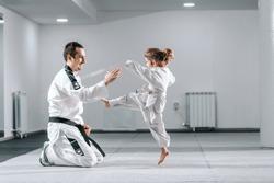 Smiling Caucasian taekwondo trainer in dobok kneeling and holding hand up while little girl kicking him.