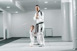 Smiling Caucasian taekwondo trainer posing with little girl in white gym.
