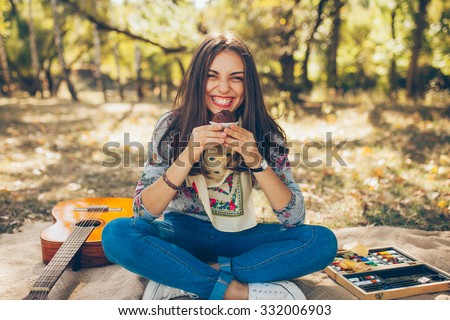 Smiling caucasian teen hipster girl sitting outdoors with guitar. Creative artistic young woman wearing casual clothes having a picnic with cupcake on autumn day.