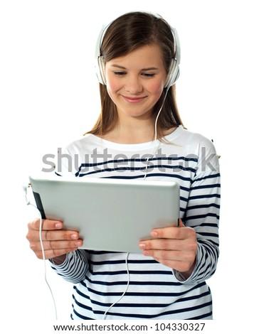 Smiling caucasian teenager enjoys listening to music. Studio shot