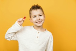 Smiling caucasian toddler boy looking to the camera and holding jelly gummy bear in his hand. Isolated on yellow background studio shot. Concept of children's delicacy.