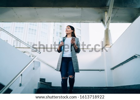 Smiling caucasian trendy dressed woman walking on ueab architecture staircase holding mobile phone ,positive hipster girl in stylish wear using navigation app on smartphone connected to 4G internet