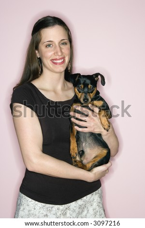Smiling Caucasian woman holding Miniature Pinscher dog standing against pink background.