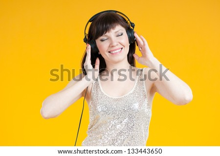 Smiling caucasian woman listening to music in headphones, yellow background