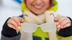 Smiling caucasian woman takes off frozen glasses outdoors in winter. The girl is cold.