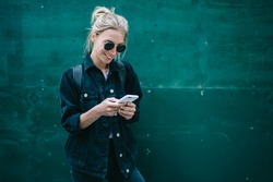 Smiling caucasian young woman sending message on smartphone standing near promotional copy space background, positive trendy hipster girl blogging in social network using mobile phone with internet