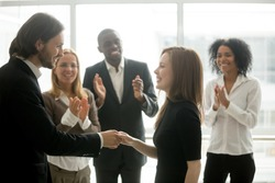 Smiling ceo promoting rewarding handshaking motivating female worker congratulating with promotion or success showing respect while team applauding, appreciation and employee recognition concept