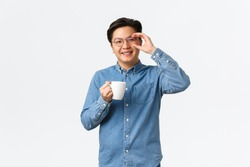 Smiling cheerful asian guy, office worker in glasses having lunch break, standing with cup of coffee over white background. Man drinking from mug and looking upbeat, morning routine