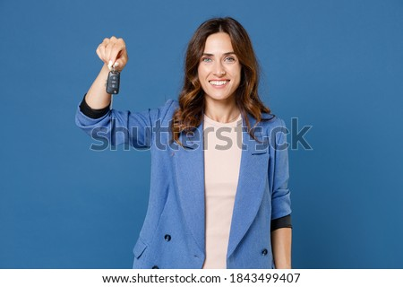 Smiling cheerful beautiful attractive young brunette woman 20s in basic casual jacket standing holding in hand car keys looking camera isolated on bright blue colour wall background studio portrait Foto stock ©