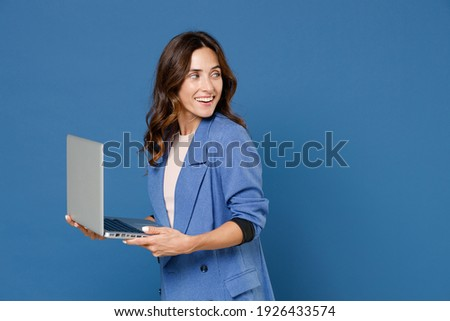 Smiling cheerful beautiful attractive young brunette woman 20s wearing basic jacket standing working on laptop pc computer looking aside isolated on bright blue colour wall background studio portrait