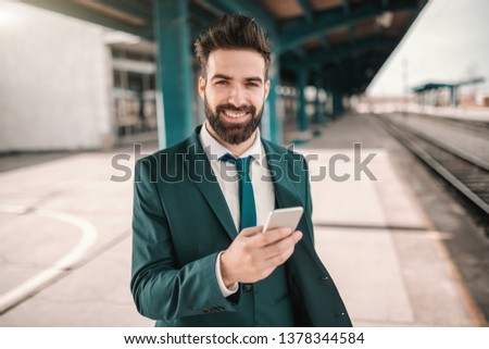 Smiling cheerful Caucasian bearded Caucasian businessman using smart phone and waiting for train while looking at camera. Follow your dreams, they know the way. #1378344584