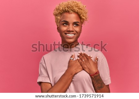 Smiling cheerful dark skinned young female keeps palms on heart, expresses appreciation, pleasure and gratitude, depicts symbol of fight against breast cancer on pink wall. Confession in love concept