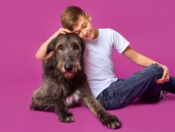 Smiling cheerful eleven years teen in white t-shirt and jeans with brown  big dog on fuchsia color background in photo studio. Pets, friendship concept