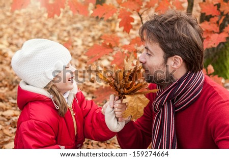 Smiling, cheerful father and daughter having fun outdoor in the park during autumn - close up portrait of happy loving active caucasian family in nature