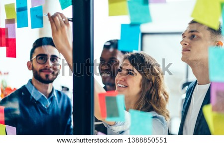 Smiling cheerful female entrepreneur writing funny information on paper stick while enjoying cooperation with male entrepreneur colleagues, multicultural people creating new strategy for proud ceo