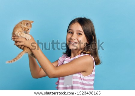 smiling cheerful girl enjoying playing with a kitten, lifestyle, spare time, free time. close up photo. animal lover
