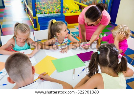 Smiling cheerful glad kids drawing together with tutor at hobby group indoors