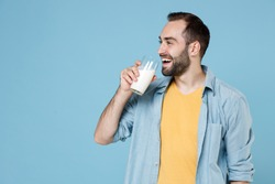 Smiling cheerful handsome young bearded man 20s wearing casual clothes posing holding in hand glass drinking vegan milk looking aside isolated on pastel blue color wall background studio portrait