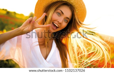 Smiling cheerful long-haired girl with curly hair breathes full breast and enjoys freedom,standing next to garden. Portrait of adorable young woman in white blouse and denim shorts having fun outside