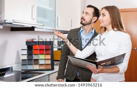 Smiling cheerful  pleasant  polite saleswoman helping man to choose materials for kitchen furniture in shop