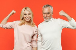 Smiling cheerful strong couple two friends elderly gray-haired man blonde woman in white pink casual clothes standing showing biceps muscles isolated on bright orange color background studio portrait