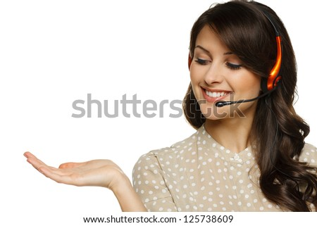 Smiling cheerful woman in headset holding empty copy space on her open palm, looking at palm, isolated on white background