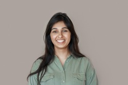 Smiling cheerful young adult indian woman looking at camera, happy pretty funny lady model laughing, feeling positive emotion standing isolated on brown background, face front headshot portrait.