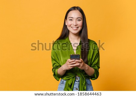 Smiling cheerful young brunette asian woman wearing basic green shirt standing using mobile cell phone typing sms message looking camera isolated on bright yellow colour background, studio portrait