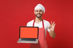 Smiling chef cook baker man in striped apron t-shirt toque chefs hat isolated on red background. Cooking food concept. Mock up copy space. Hold laptop pc computer with blank screen showing OK gesture