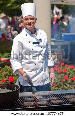 smiling chef cooking burgers outdoors on a nice summer day