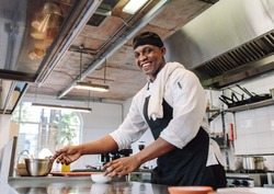 Smiling chef cooking food at restaurant kitchen. African male cook standing by kitchen counter looking at camera and smiling.