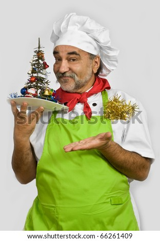 smiling chef  holds  New Year tree in hand - stock photo
