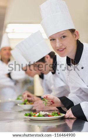Smiling chef looking up from preparing salad in culinary class