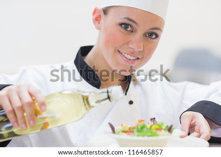 Smiling chef preparing a salad in the kitchen