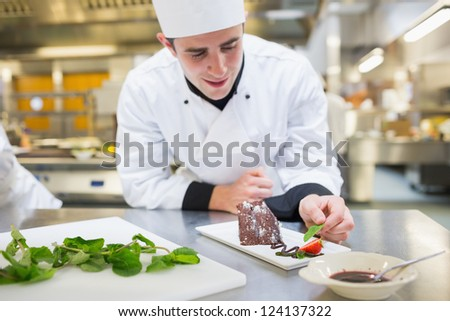 Smiling chef putting mint with his dessert in the kitchen